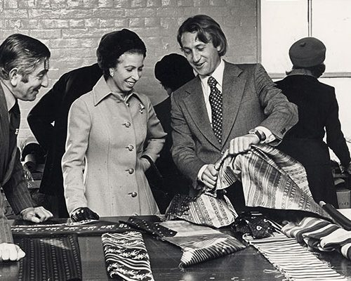 Princess Anne inspecting silk fabric inside Stephen Walters fabric mill
